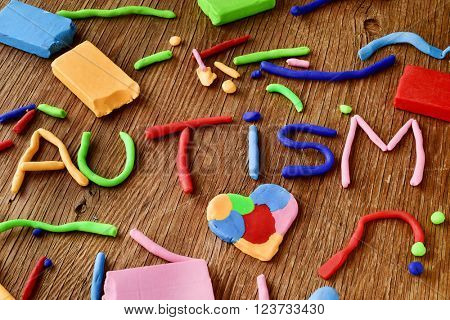 the word autism made from modelling clay of different colors on a rustic wooden surface