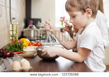 Smiling Small Boy Whisking Eggs In Bowl On Table