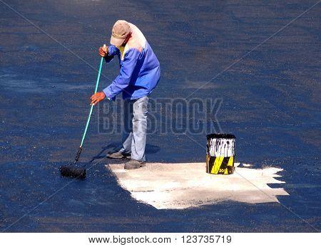 Man applying waterproofing glue on roof with a broom