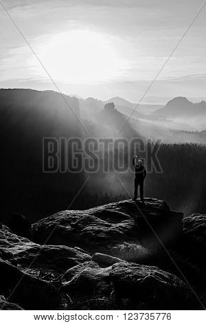 Hiker Is Taking Photo By Smart Phone On The Peak Of Mountain At Spring Sunrise. Sharp Cliff Above De