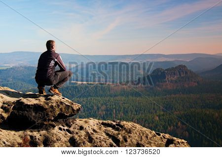Young man in black sportswear sit on cliff edge and look into red Sun at horizon over misty valley ** Note: Visible grain at 100%, best at smaller sizes