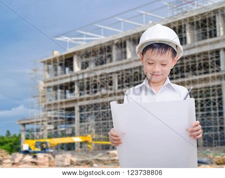 Young asian boy pretend to be engineer at construction site