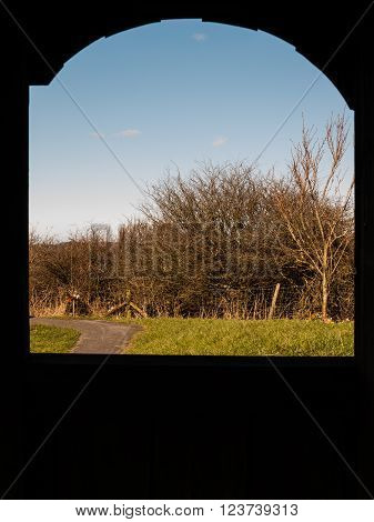 A landscape is visible through a rural archway.