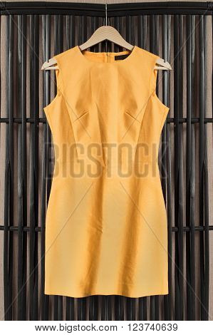 Yellow sleeveless dress on clothes rack hanging on wooden screen