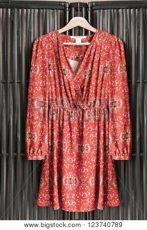 Silk red dress on clothes rack hanging on wooden screen