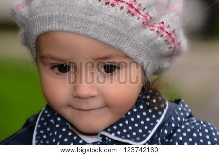 Young girl wearing warm wool hat with cheeky smile. A small child looks mischievous, with large dark eyes and polka dot coat