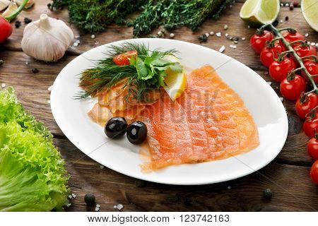 Salty smoked salmon, restaurant food. Fish dish, banquet, catering served plate at rustic wood with vegetables at background. Salted salmon fish sliced with black olives.