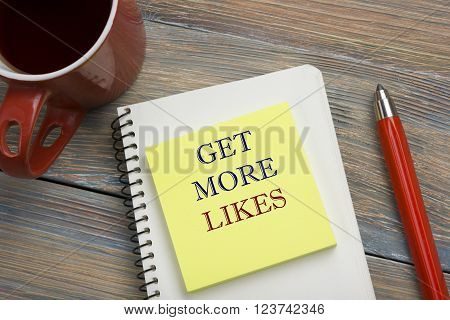 Get More Likes concept. Notebook page with text, red pencil and coffee cup. Office desk table top view.