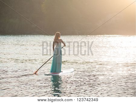 SUP the girl in a white dress with a paddle board floats on water setting sun
