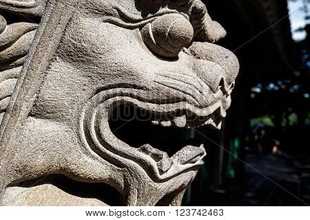 Waikiki, Honolulu, Hawaii, USA - December 13, 2015: Closeup view of the head of a stone lion seen along a public access at the Hilton Hawaiian Village. The statue symbolically represents power, and it guards against evil energies.