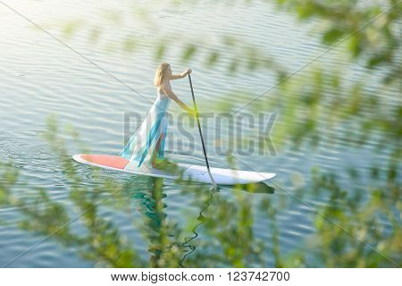 SUP the girl in a white dress with a paddle board floats on water view through branches