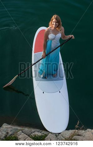 SUP the girl in a white dress with a paddle board floats on water near the shore