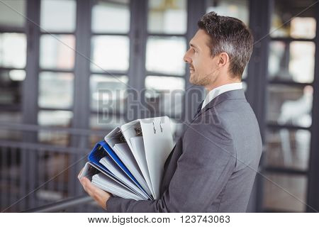 Side view of businessman carrying files stack in office