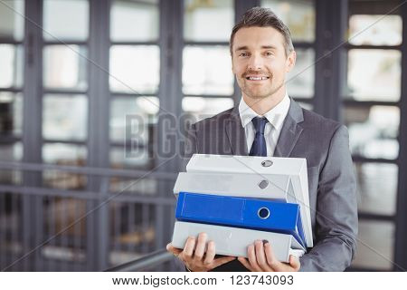 Portrait of businessman carrying files stack in office