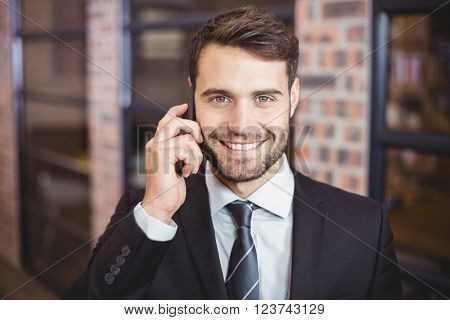 Close-up portrait of happy businessman talking on cellphone in office