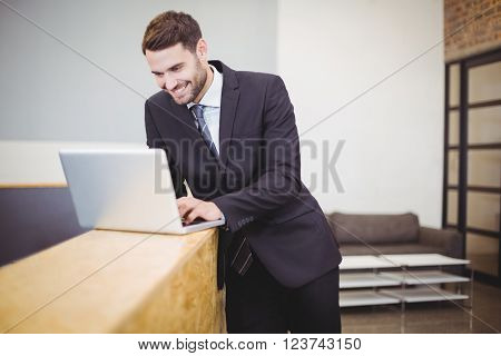 Happy businessman using laptop while leaning on counter at office