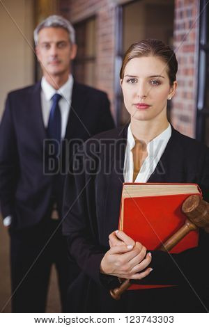Portrait of female lawyer with male colleague standing in background