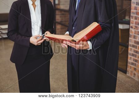 Midsection of male lawyer with female colleague discussing over book in office