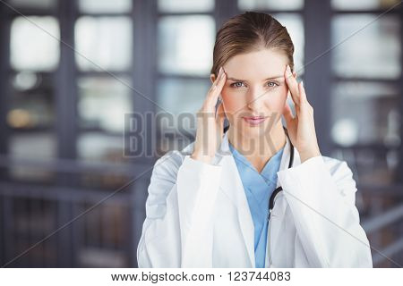 Portrait of tensed female doctor with head in hands while standing in hospital