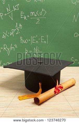 Gortarboard and graduation scroll, on the background of school board