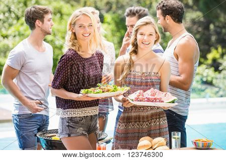 Friends preparing for outdoors barbecue party near pool
