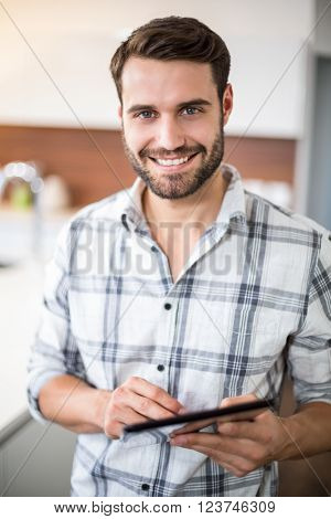 Close-up portrait of happy young man using digital tablet in kitchen