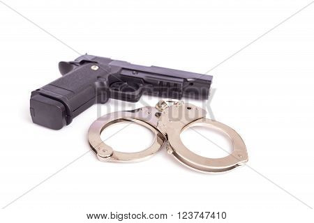 Close Up Gun And Handcuffs Isolated On White