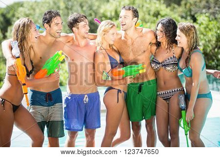 Happy friends standing together near swimming pool with water guns