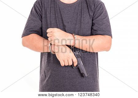 Close up man with handcuffs and gun on hands isolated on white background