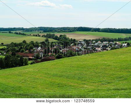 Hessian summer landscape with a village among the green fields near Hanau, Germany