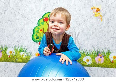 Pleased Child Playing With Fitness Ball In Kindergarten