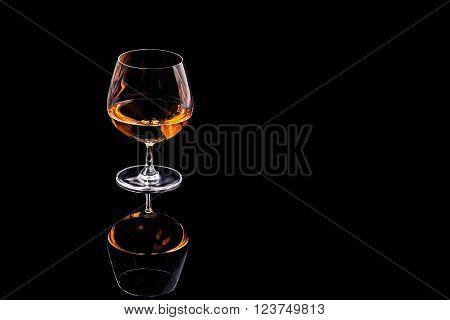 A glass of brandy on a black background