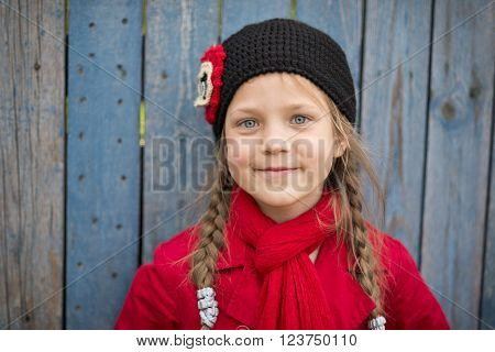portrait of smiling girl in red raincoat and scarf near wooden fence