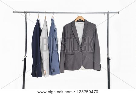 Set of men's suits hanging on a white background