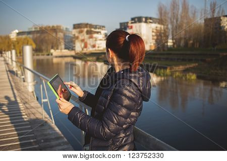 Yung woman student taping on tablet using tablet in a city park near river.Young smiling student outdoors with tablet.Life style.City