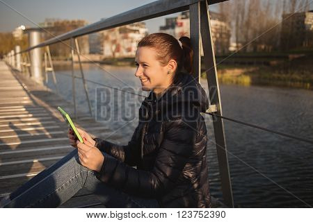 Smiling young woman student taping on tablet using tablet while sitting on a city bridge near river.Young smiling student outdoors with tablet.Life style.City