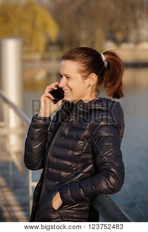 Smiling young womanstudent talking to phone in a city park near river.Young smiling student outdoors with mobile phone.Life style.City