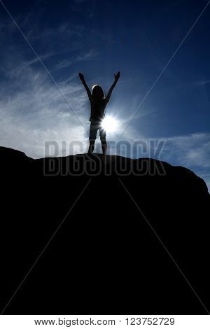 Silhouette of hiker at the top of a peak with blue sky in background