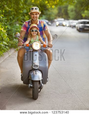 Happy young father and little daughter riding a vintage scooter in the street wearing hats and sunglasses. Holiday and travel concept
