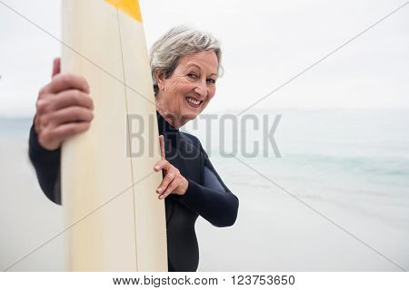 Senior woman in wetsuit holding a surfboard on the beach on a sunny day