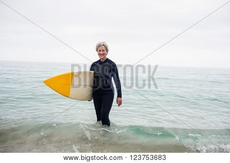 Senior woman in wetsuit standing in water with surfboard on the beach on a sunny day