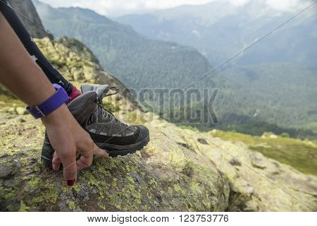 The man in the mountains showing his hand to unstick sole from hiking boots