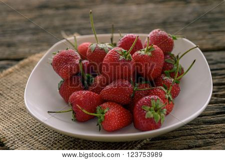 Rotten strawberries in wooden plate on wooden table on blurred background ** Note: Soft Focus at 100%, best at smaller sizes