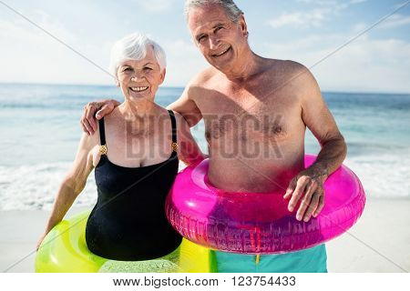 Portrait of senior couple in inflatable ring standing on beach