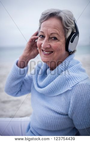 Portrait of senior woman listening to music on headphone at beach
