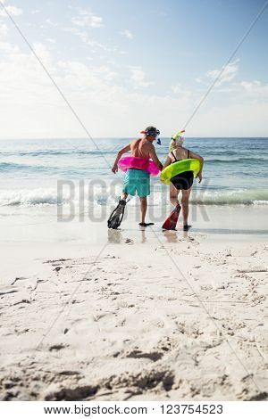 Rear view of senior couple in inflatable ring and flipper walking towards sea on a sunny day