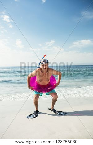 Portrait of senior man in inflatable ring and flippers standing on beach on a sunny day