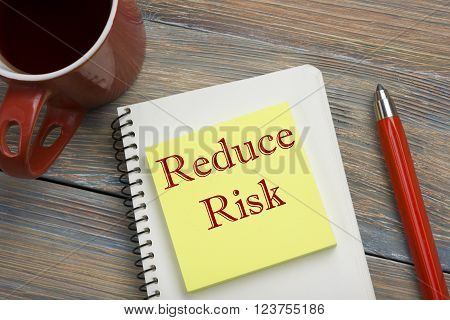 Risk management strategies - avoid, exploit, transfer, accept, reduce, ignore. Office desk table with notebook, pen and cup of coffee.