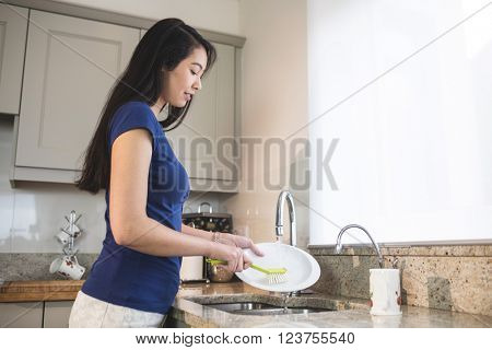 Young woman washing up in the kitchen at home