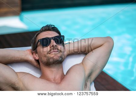 Handsome man in sunglasses relaxing on a sun lounger near pool